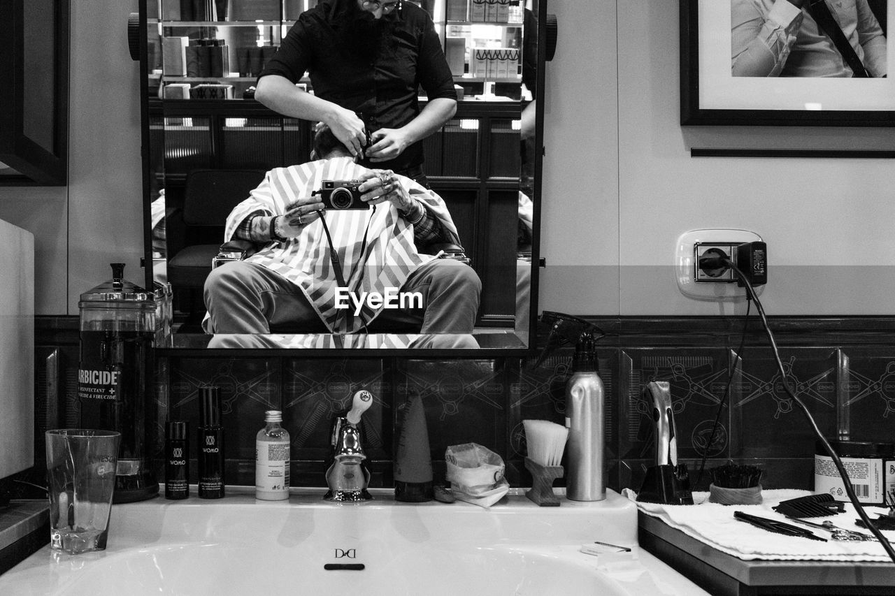 Reflection of man photographing with barber on mirror at shop