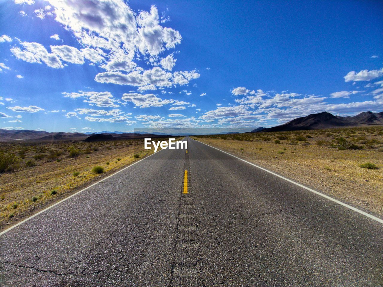 road, sky, transportation, the way forward, direction, cloud - sky, marking, diminishing perspective, vanishing point, road marking, landscape, sign, environment, nature, no people, symbol, tranquil scene, scenics - nature, tranquility, day, outdoors, dividing line, straight, arid climate