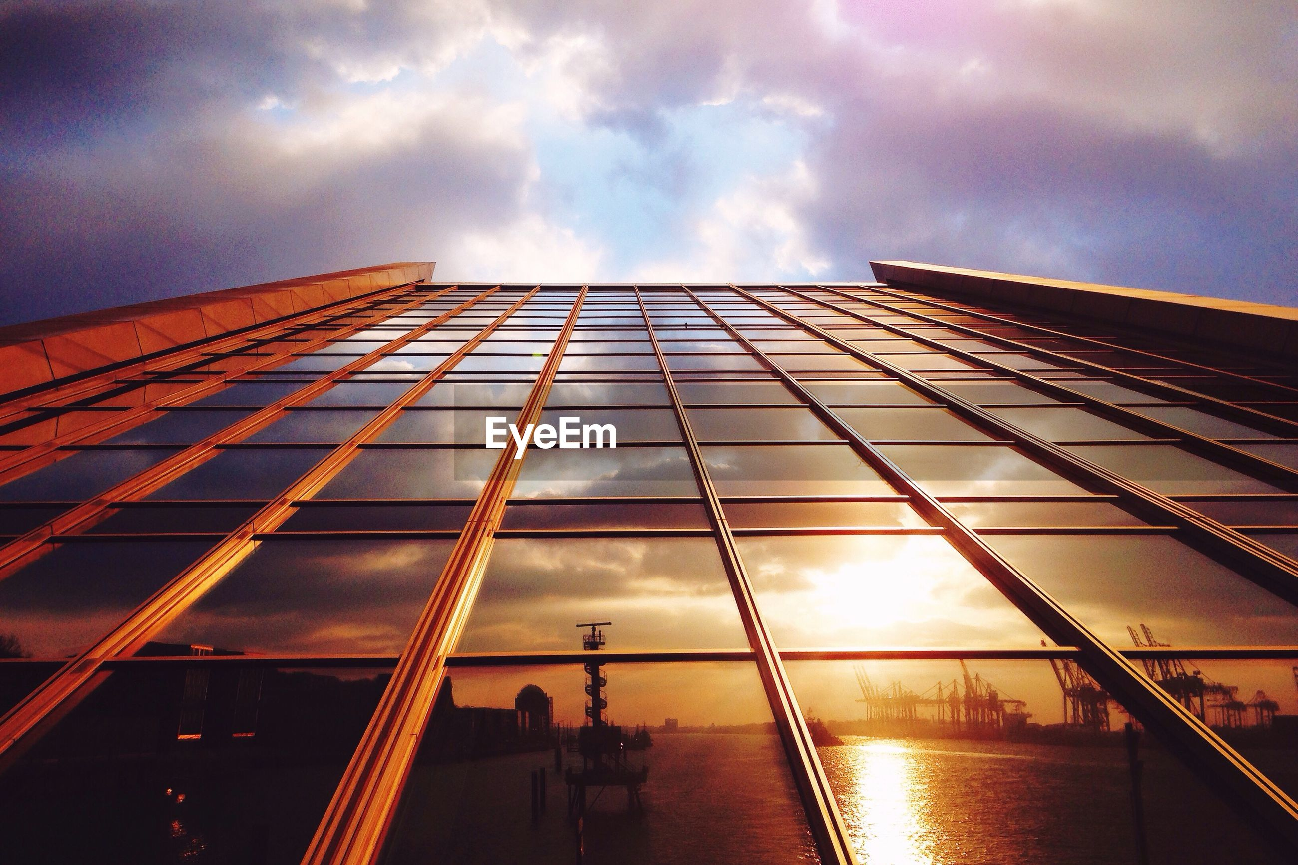Reflection of sea and cloudy sky on glass building during sunset