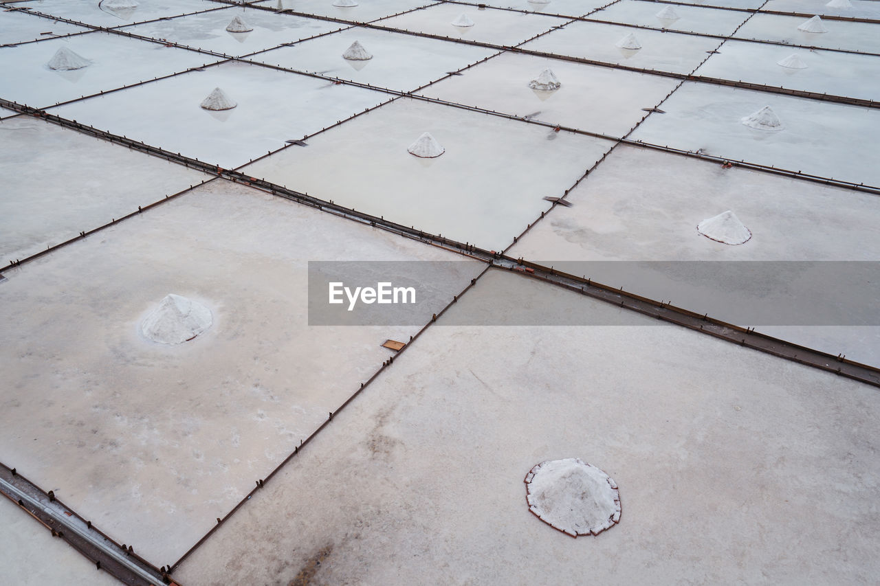HIGH ANGLE VIEW OF TILED FLOOR WITH SHADOW ON FOOTPATH