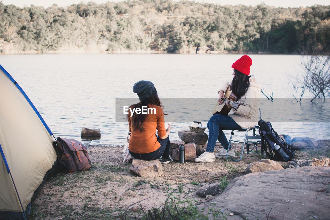 Friends Enjoying By Lake During Camping