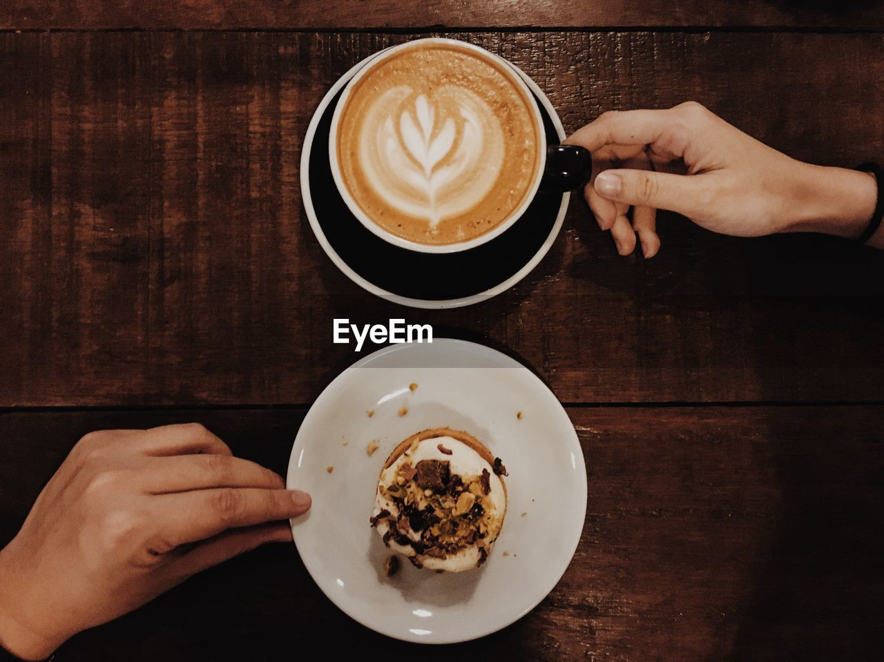 Close-Up Of Hand Holding Cappuccino Served On Table