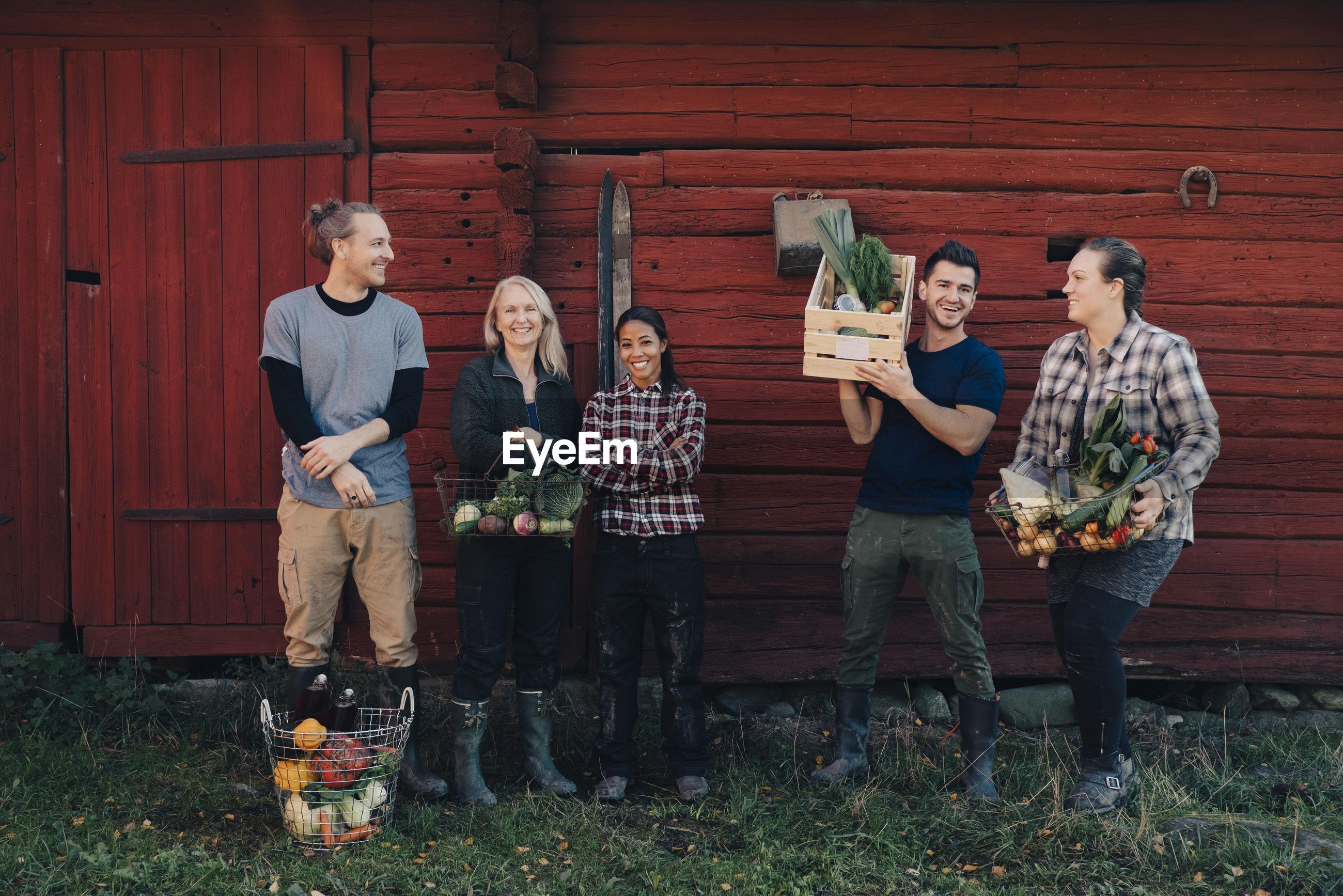 Full length of multi-ethnic farmers with organic vegetables standing against barn