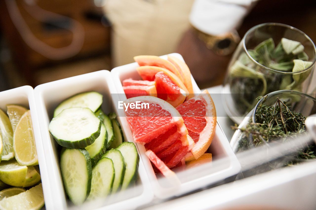 Slice of cucumber and citrus fruit with glass of leaf