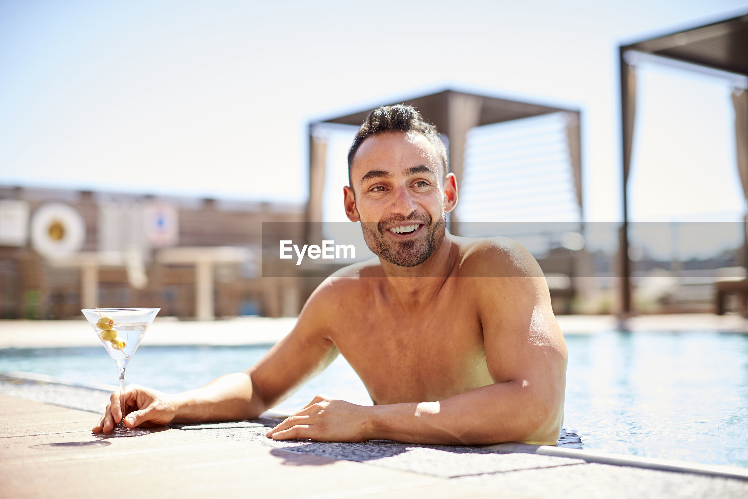 PORTRAIT OF SHIRTLESS MAN WITH WOMAN AT SWIMMING POOL