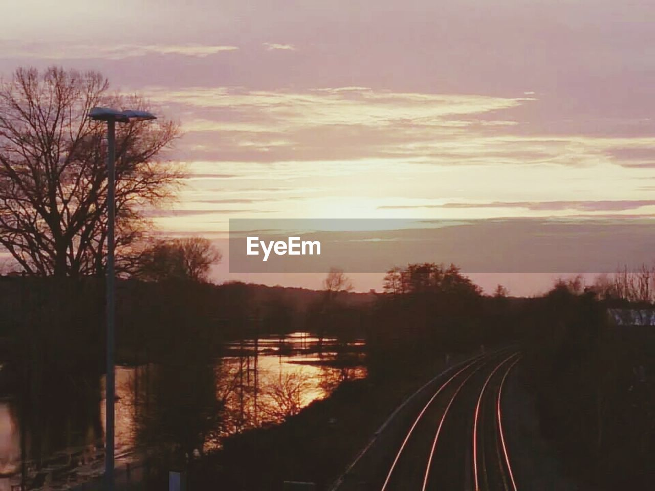 sunset, transportation, tree, sky, railroad track, no people, scenics, outdoors, nature, water, beauty in nature, bare tree, city, day