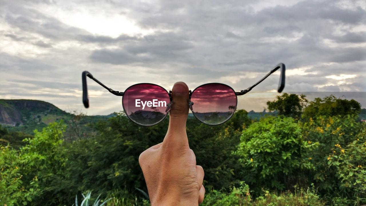 Cropped Hand Holding Eyeglasses Against Sky