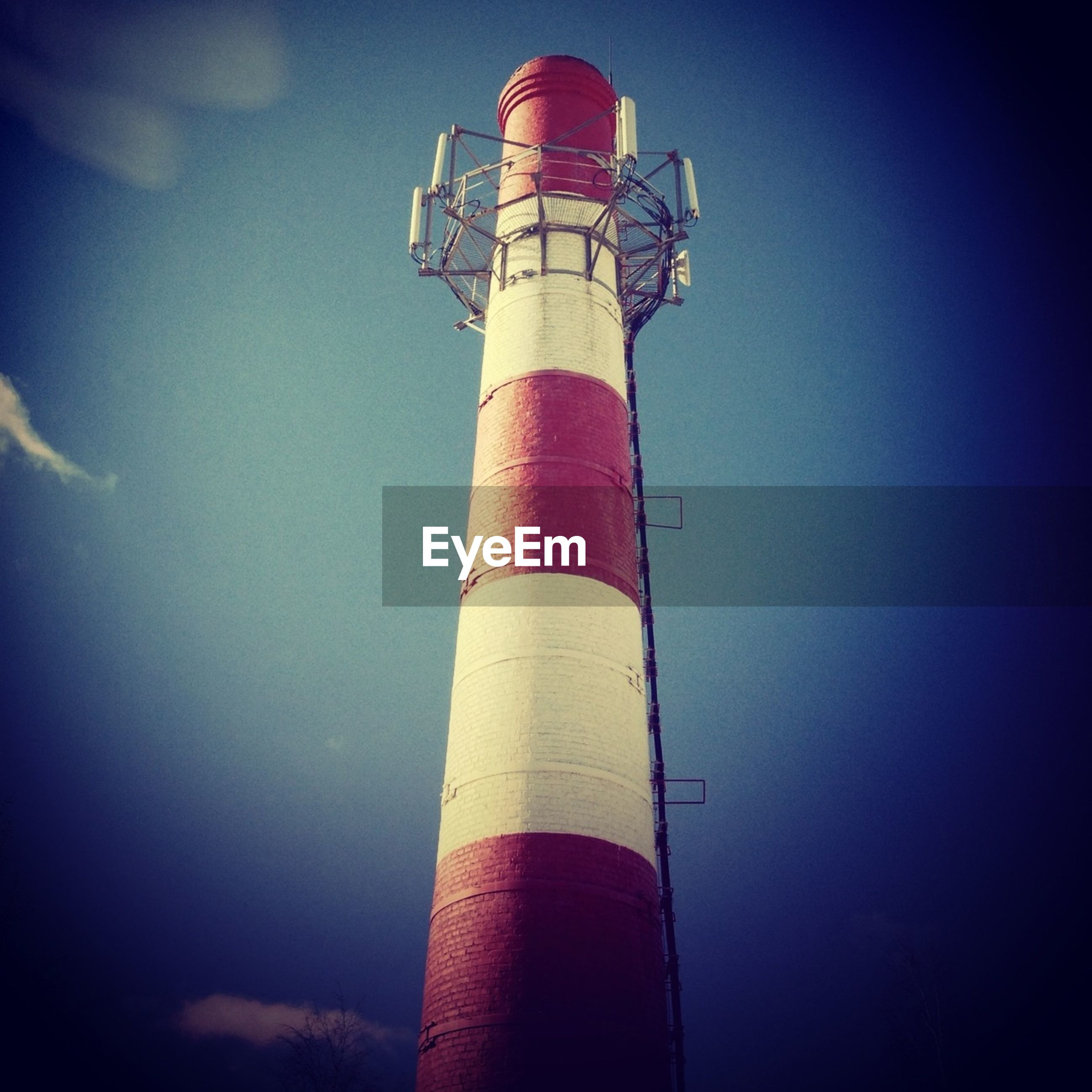 low angle view, lighthouse, guidance, tower, architecture, built structure, industry, building exterior, smoke stack, sky, direction, protection, tall - high, safety, factory, pole, security, red, blue, no people