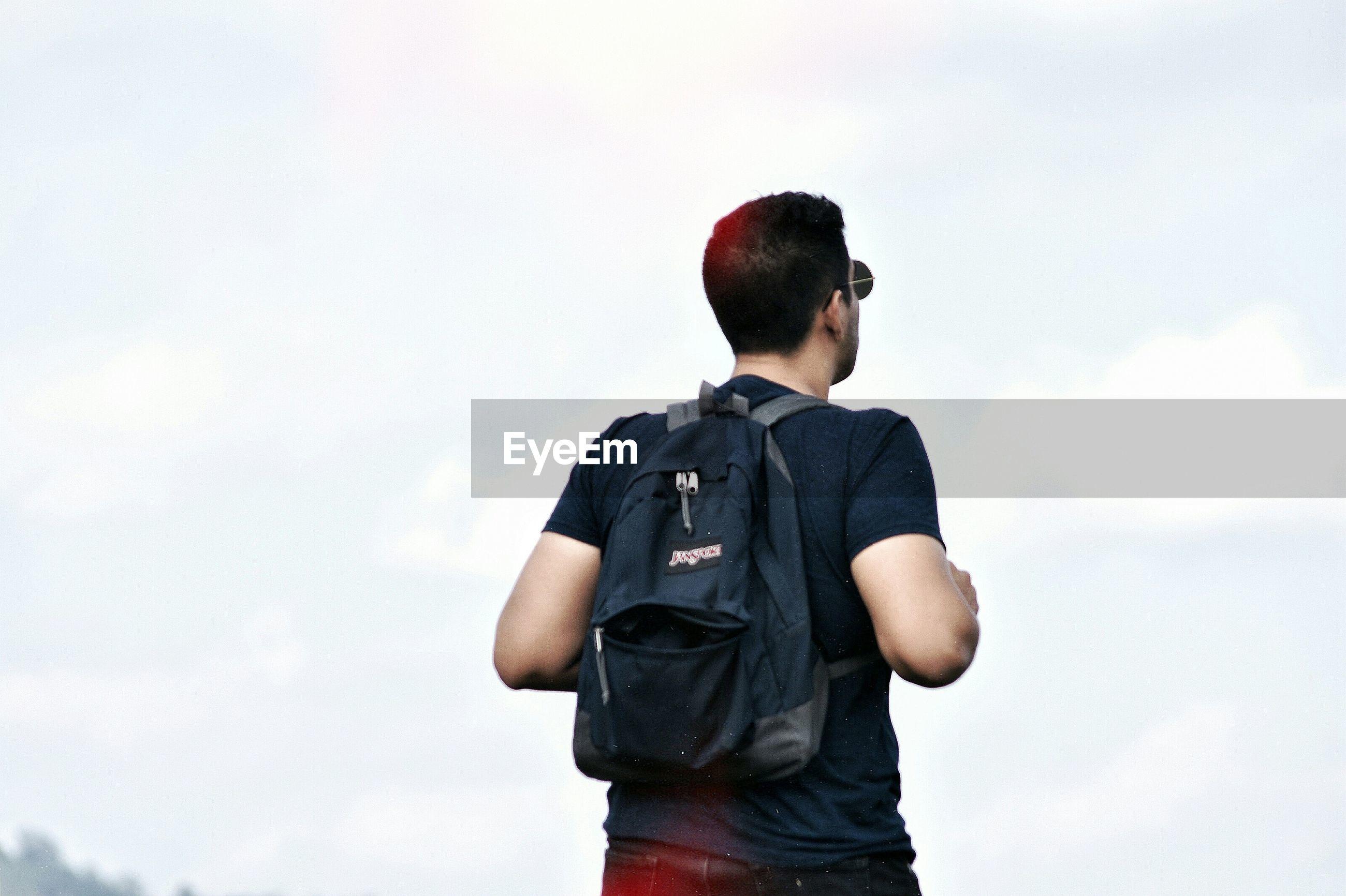 REAR VIEW OF BOY STANDING IN SKY