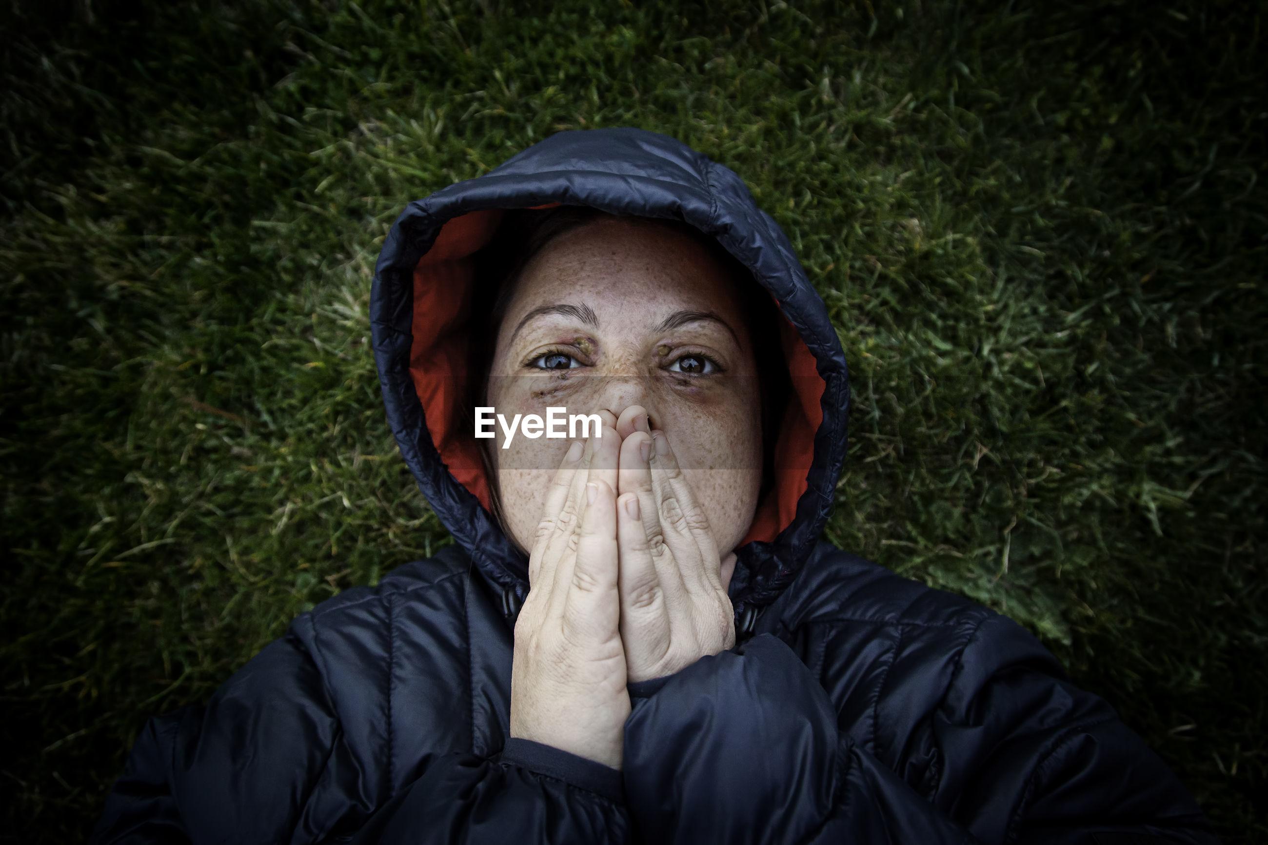 Portrait of woman wearing warm clothing on grassy field