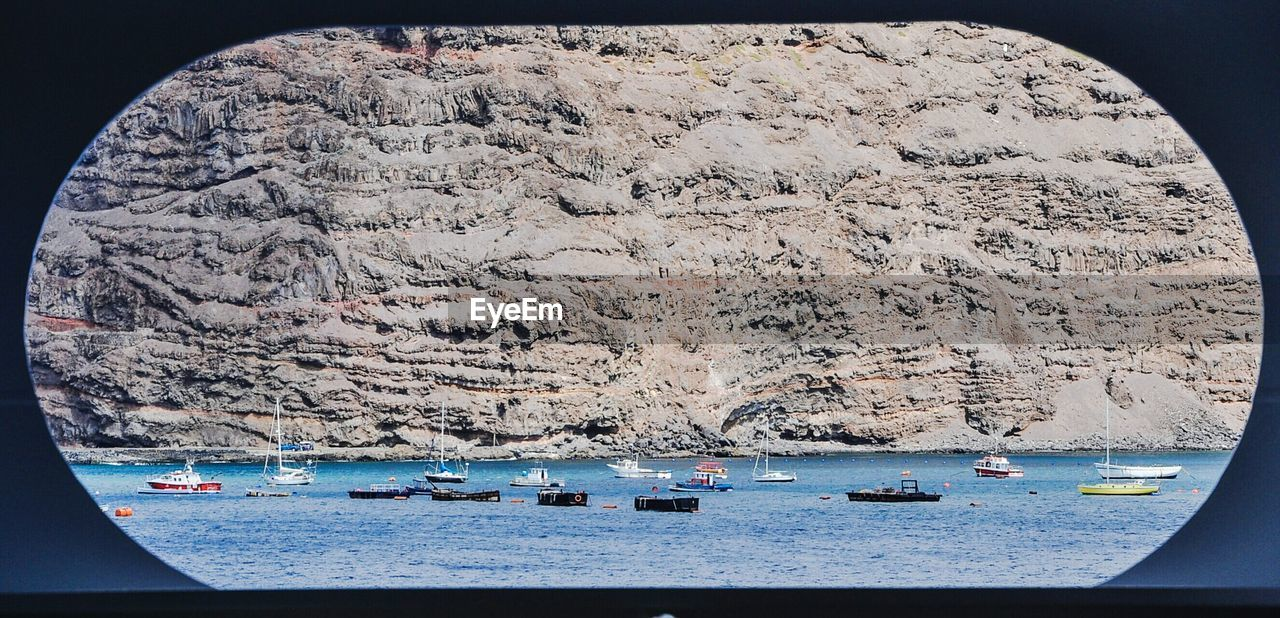 water, mode of transport, nautical vessel, sea, transportation, scenics, rock - object, nature, mountain, day, beauty in nature, no people, moored, outdoors, sky