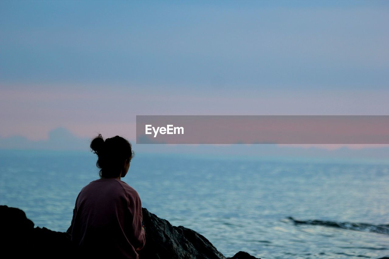 Rear view of woman sitting on rock and looking at view during sunset