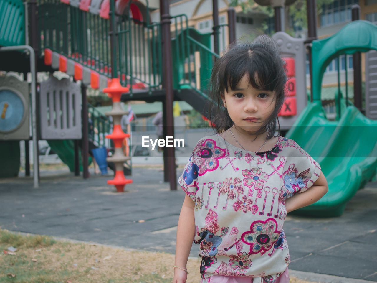 Portrait of cute girl standing against slide in playground