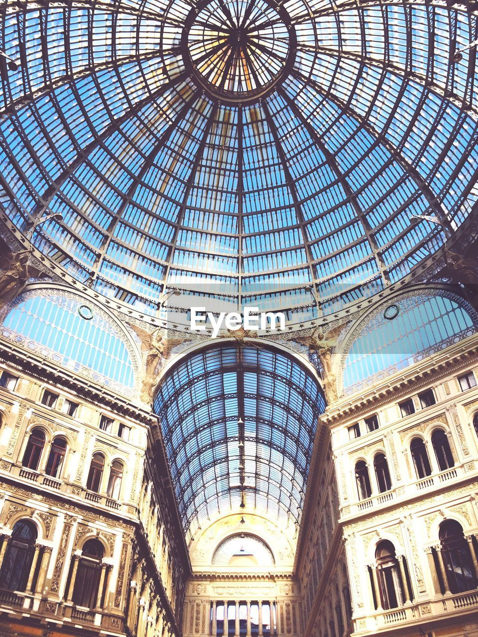 built structure, architecture, ceiling, low angle view, building exterior, arch, travel destinations, no people, sunlight, dome, the past, history, travel, shopping mall, tourism, building, pattern, city, outdoors, architectural column, skylight, ornate, architecture and art