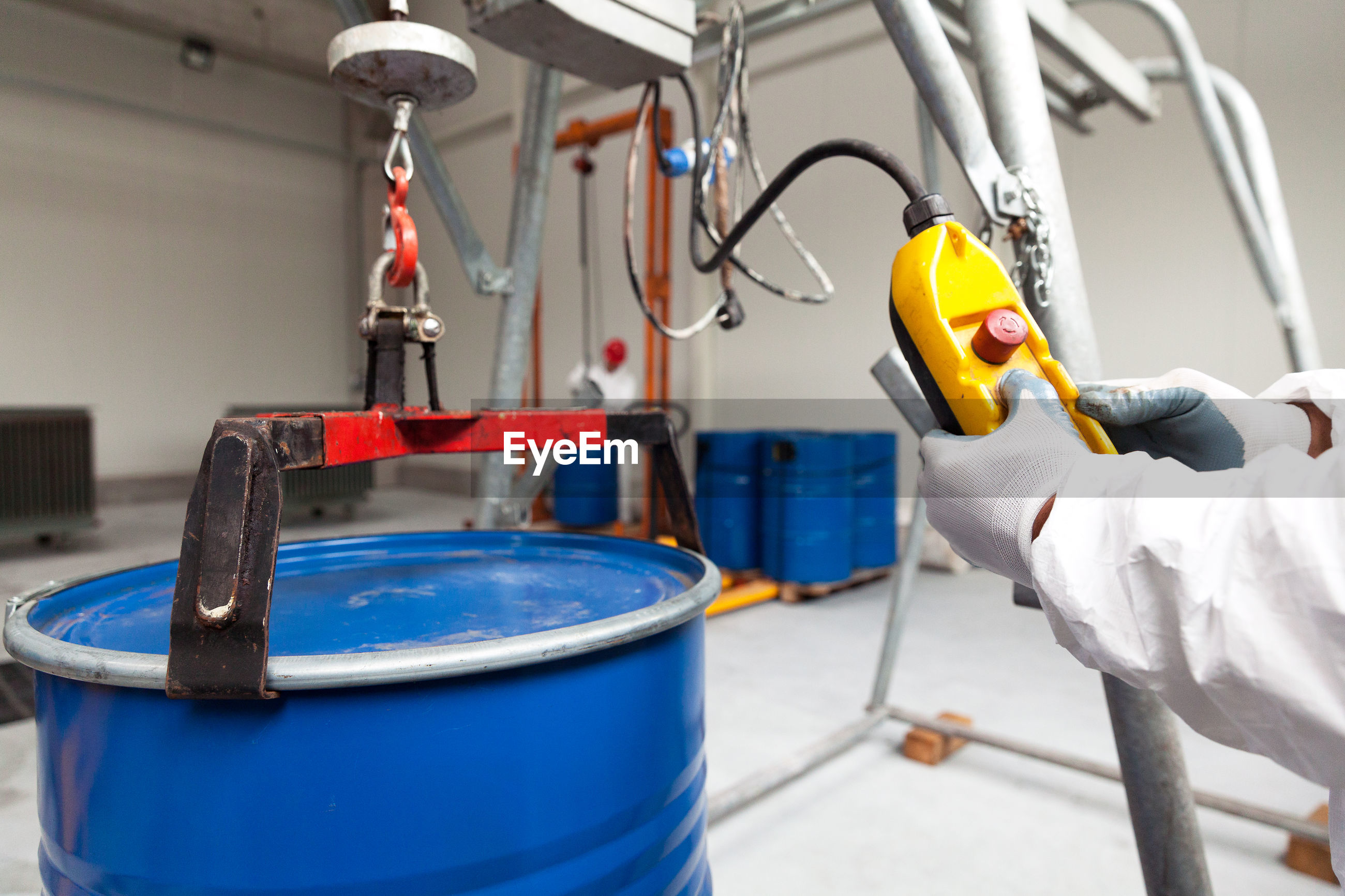 Cropped image of worker using drum lifter in warehouse