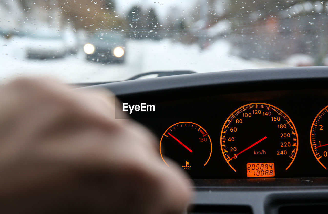 Close-Up Of Hand By Speedometer In Car
