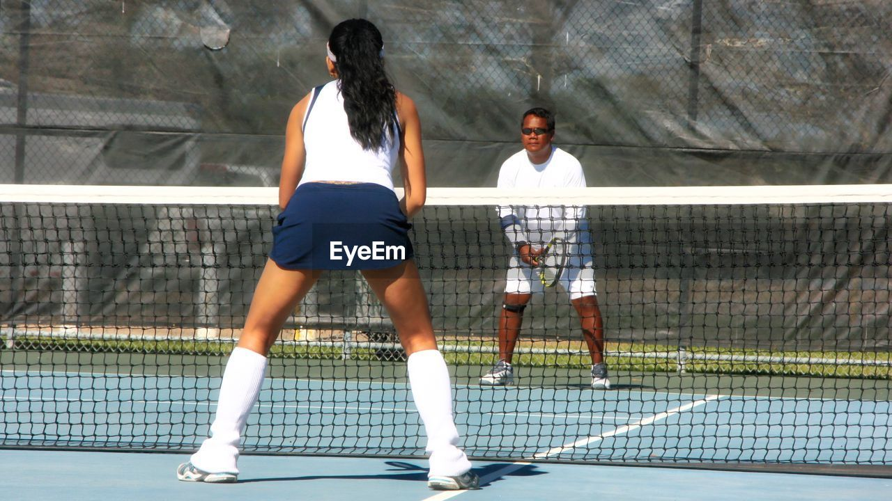 Players playing tennis in court