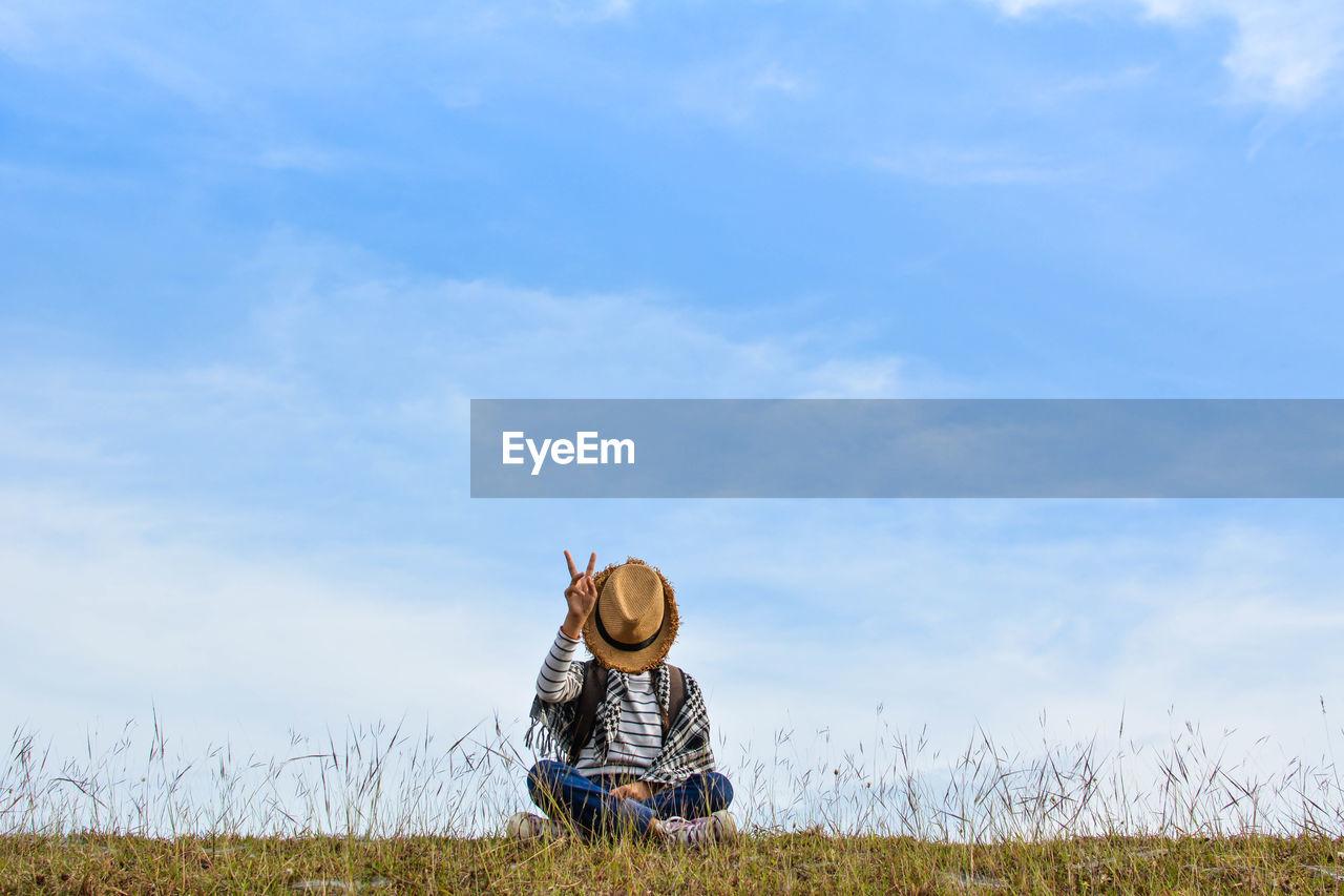 Girl Sitting On Grassy Field Against Blue Sky