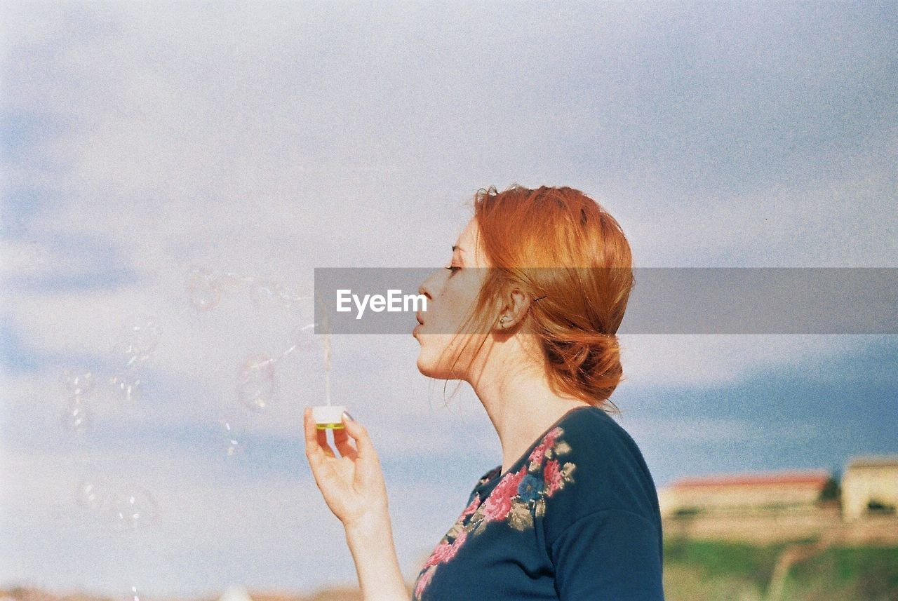 CLOSE-UP OF A Young, Red Headed WOMAN Blowing Bubbles