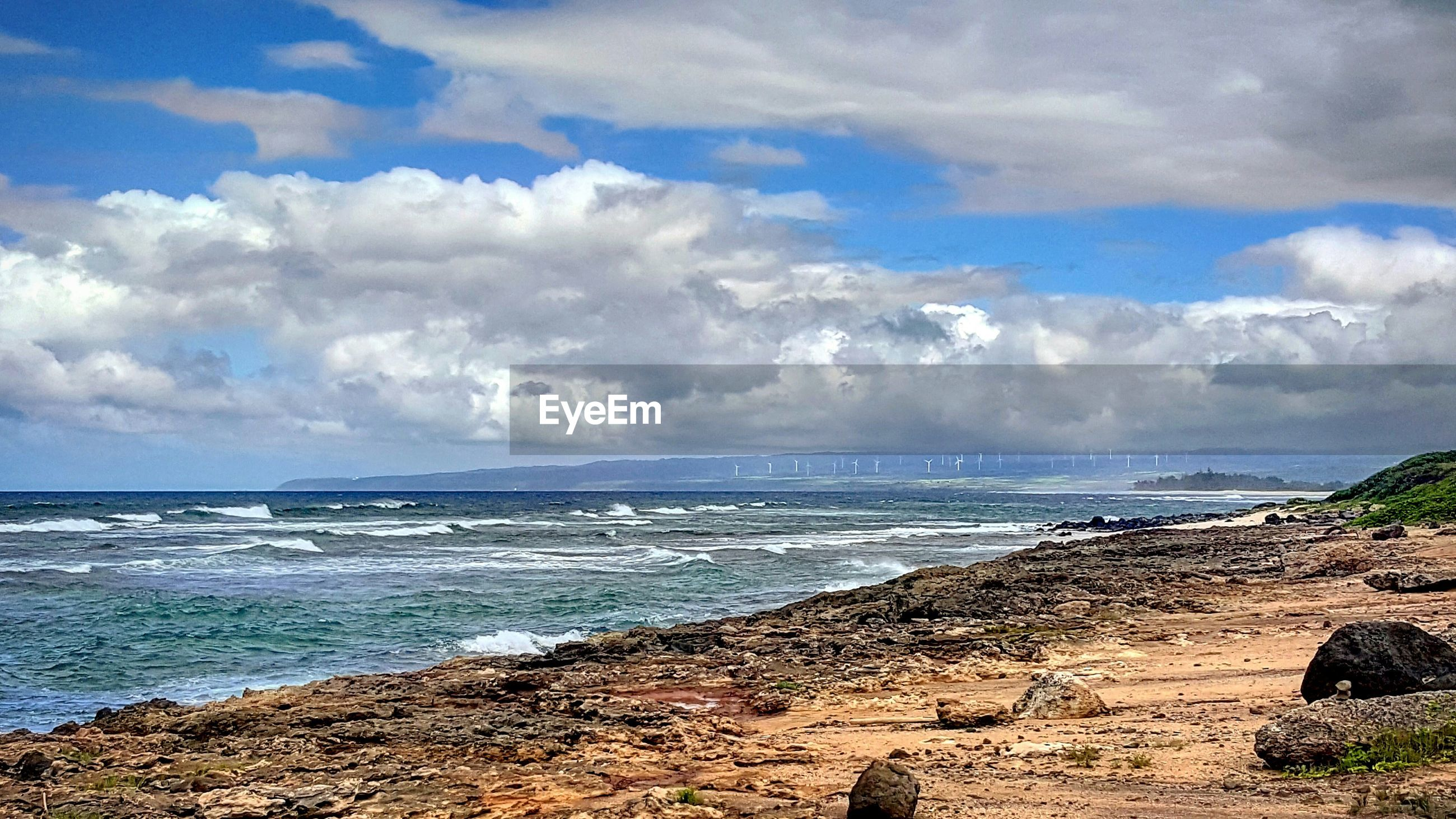 Scenic view of rocky coastline against cloudy sky