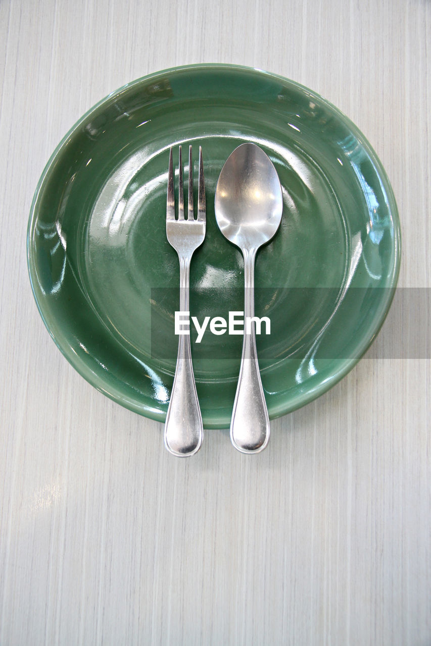 kitchen utensil, eating utensil, spoon, table, still life, indoors, household equipment, no people, food and drink, directly above, metal, silverware, empty, plate, fork, wood - material, close-up, high angle view, green color, food, silver colored, empty plate, steel, setting, crockery, alloy
