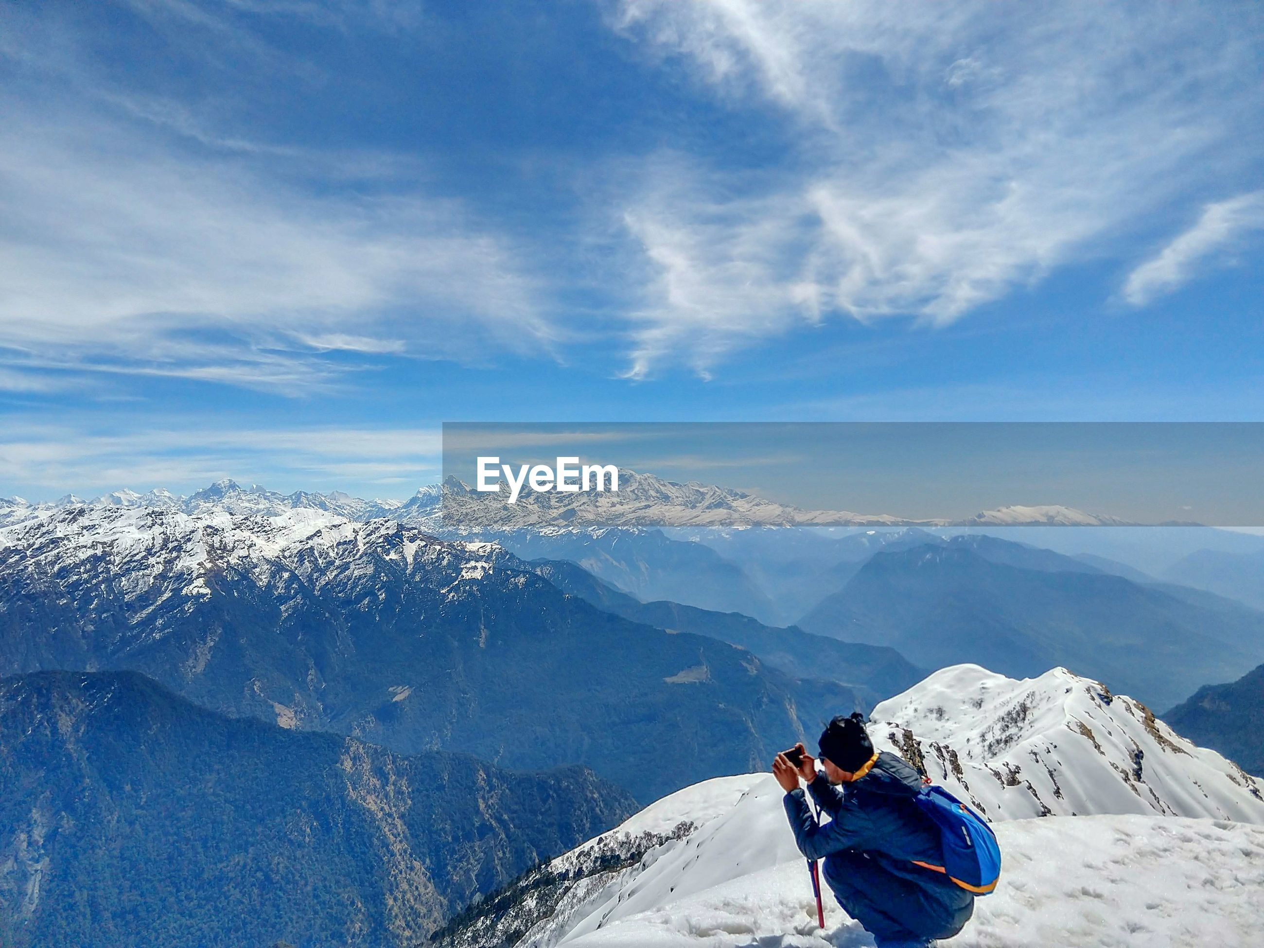 Side view of backpacker photographing on snowcapped mountain against sky