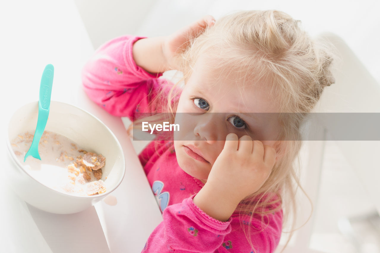 High angle portrait of sad girl sitting with breakfast cereal at table