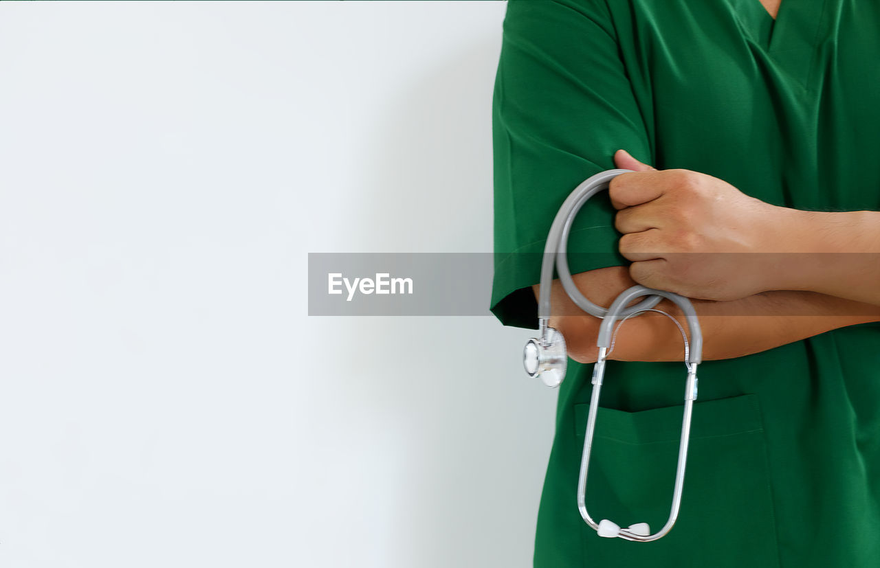 Midsection Of Doctor Wearing Scrubs While Holding Stethoscope Over White Background