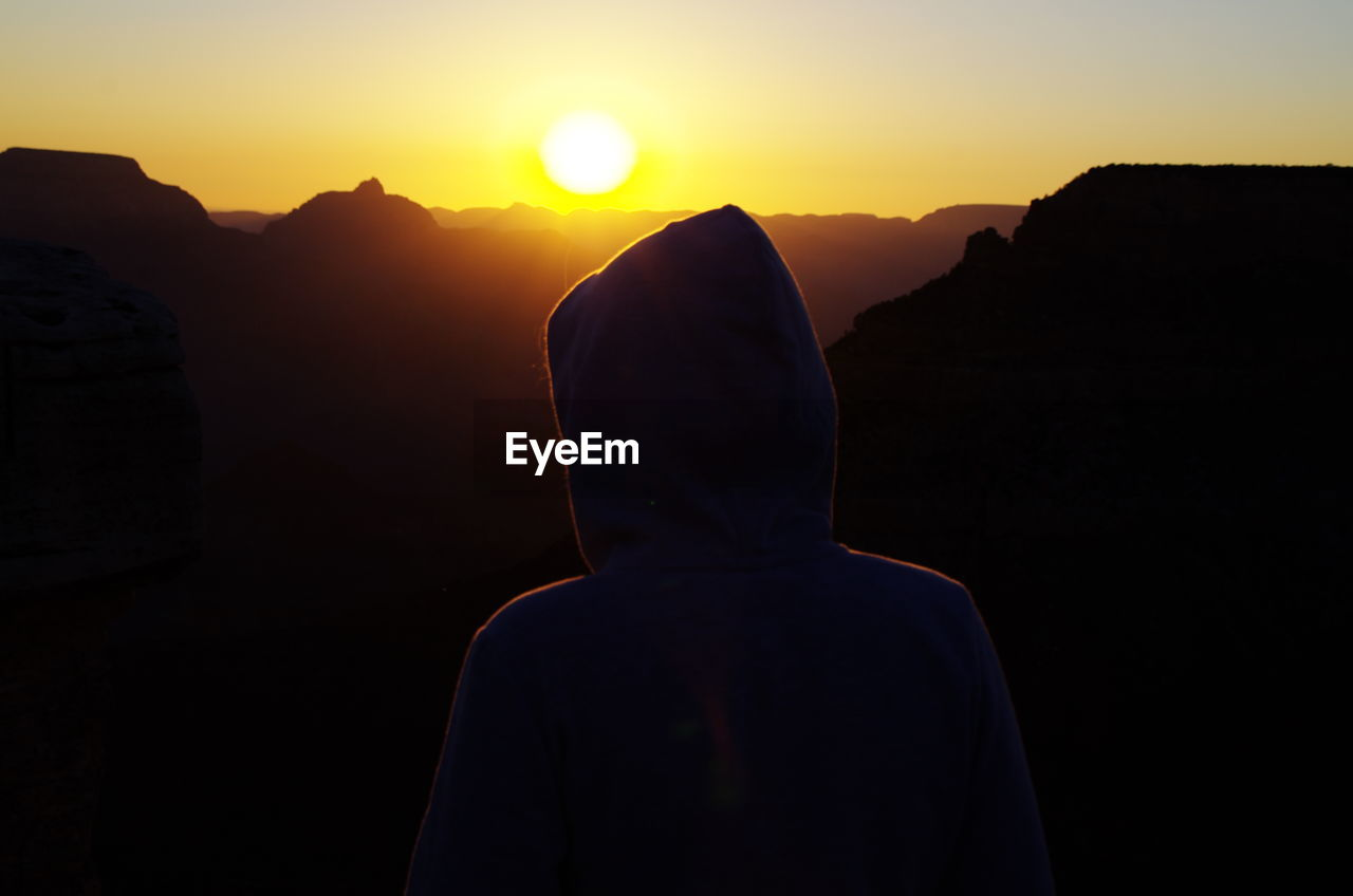 Rear View Of Person Wearing Hooded Shirt Against Sky During Sunrise