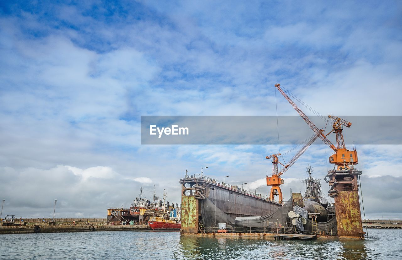 cloud - sky, sky, nautical vessel, crane - construction machinery, transportation, day, water, waterfront, mode of transport, architecture, outdoors, built structure, no people, sea, industry, building exterior, nature, drilling rig