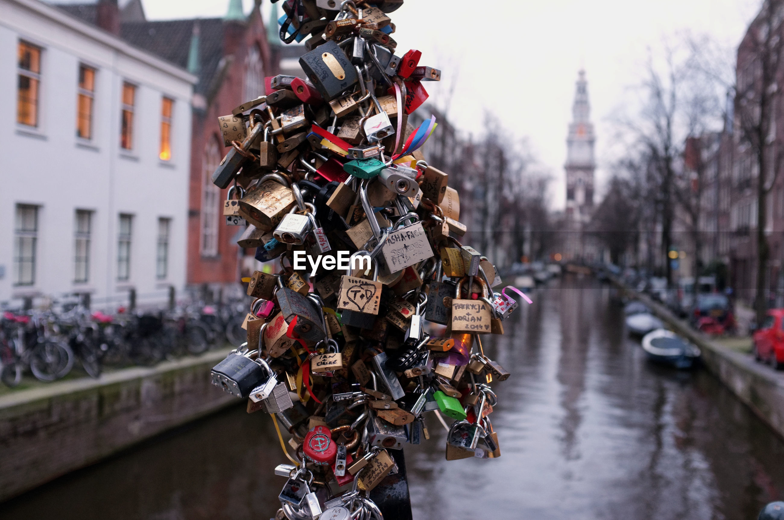 Bunch of padlocks on pole by canal