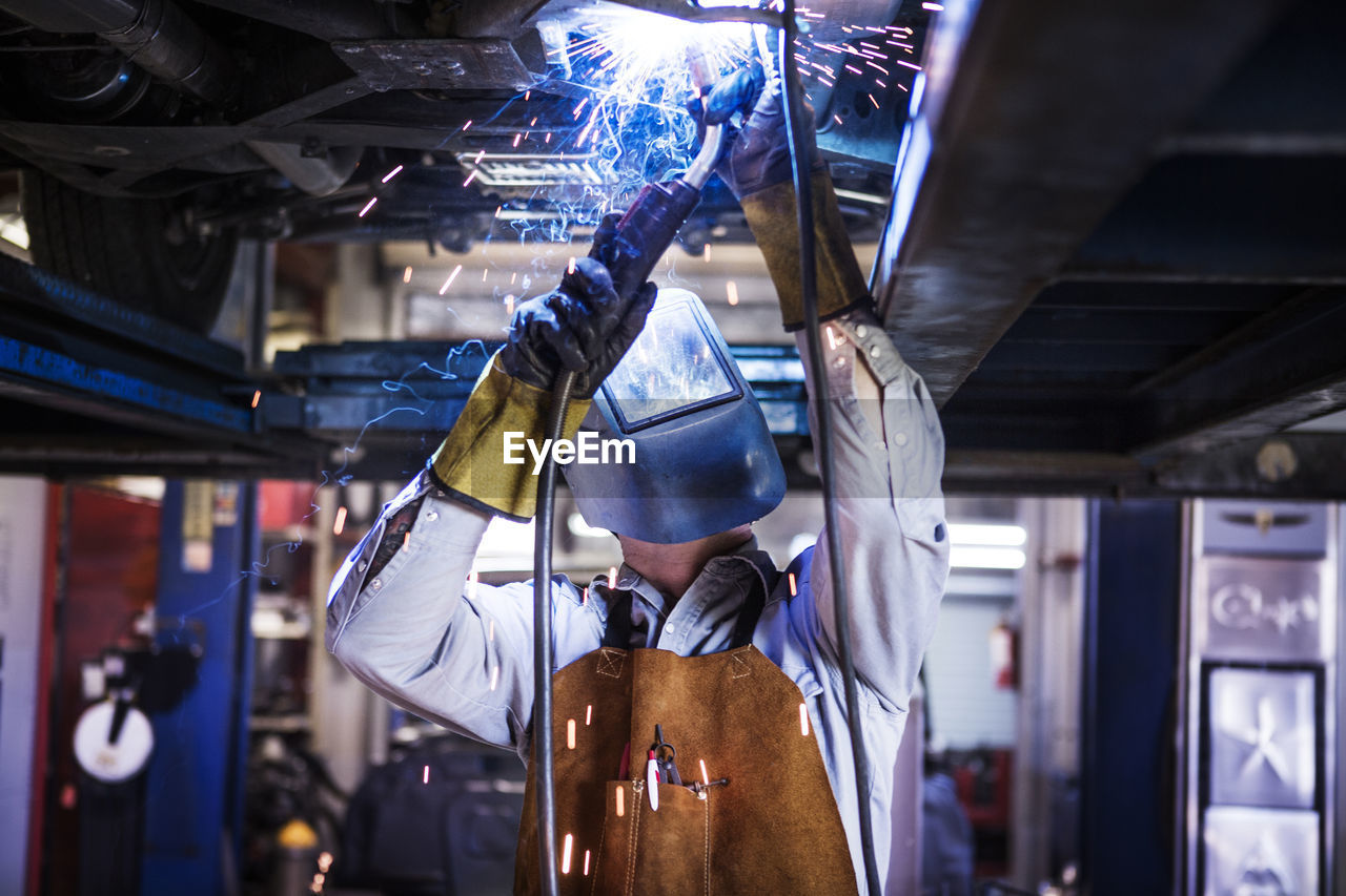 Mechanic welding while repairing car in auto repair shop