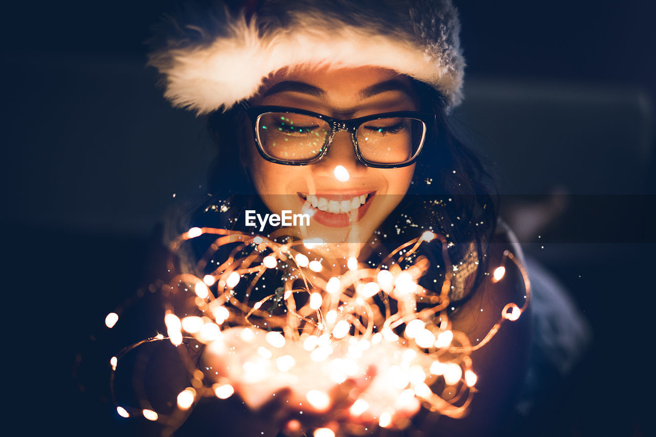 Close-Up Of Smiling Young Woman With Illuminated String Lights In Darkroom
