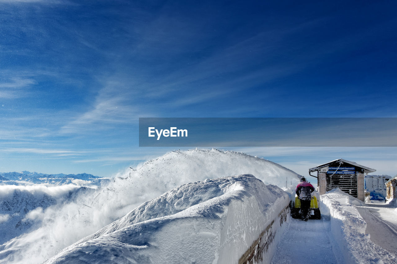 Rear View Of Man Walking On Snow Field Against Sky