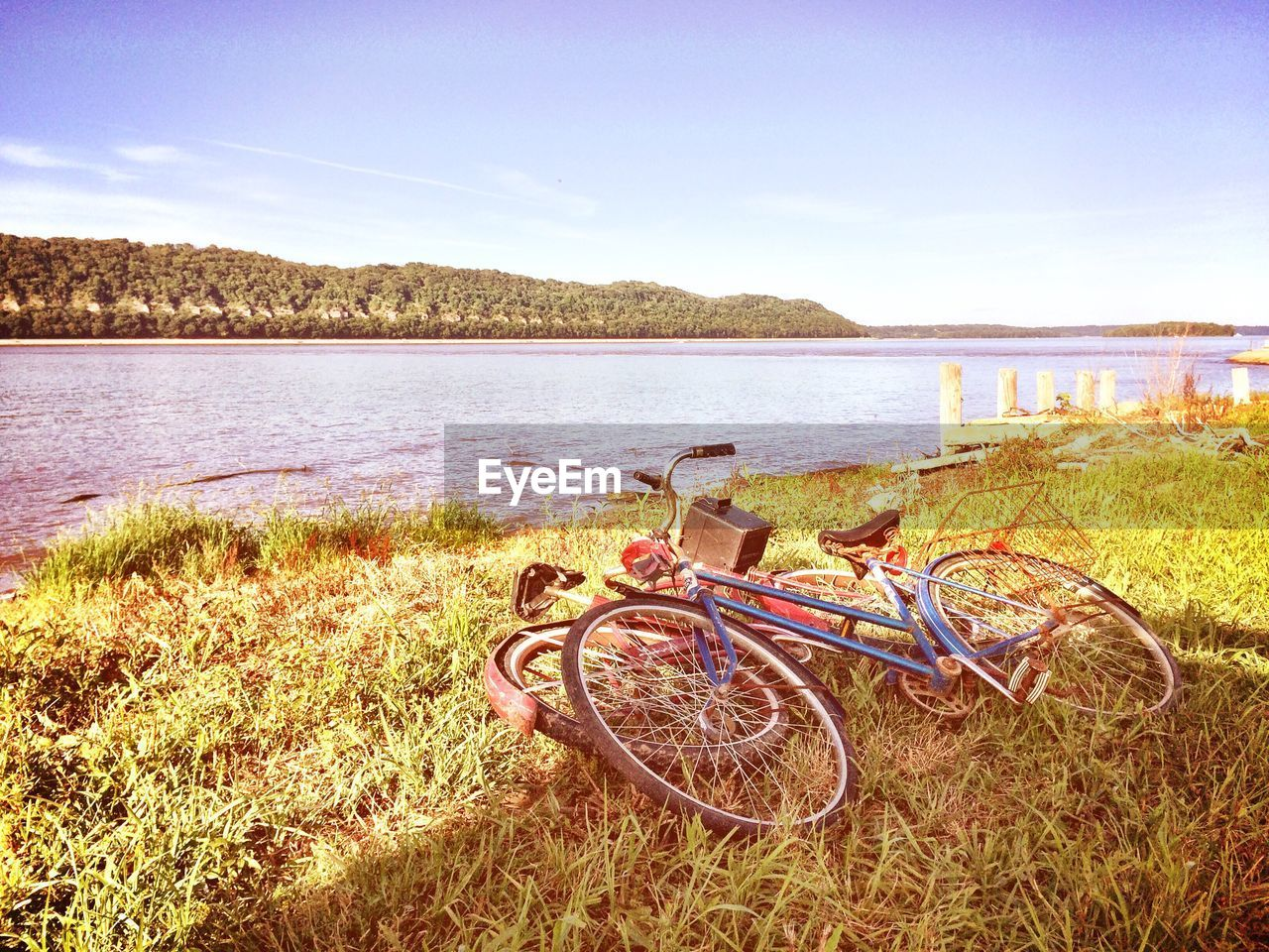 bicycle, transportation, grass, no people, mode of transport, water, outdoors, nature, lake, day, tranquil scene, land vehicle, tranquility, stationary, field, scenics, sky, beauty in nature