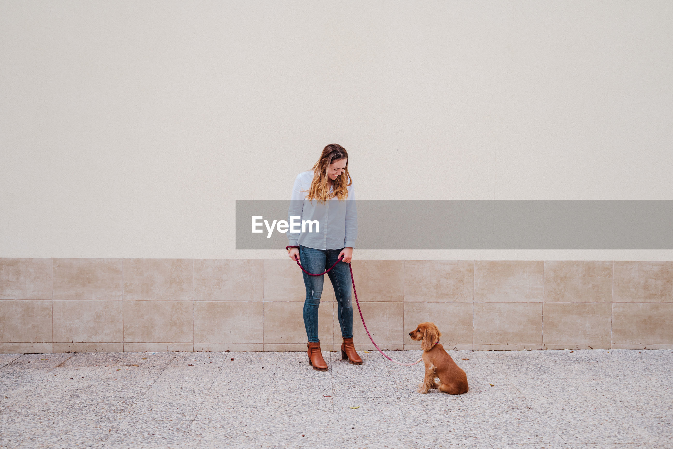 Full length of woman with dog standing on footpath