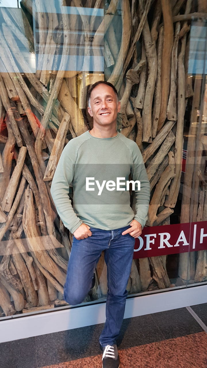 Portrait of smiling man standing against store