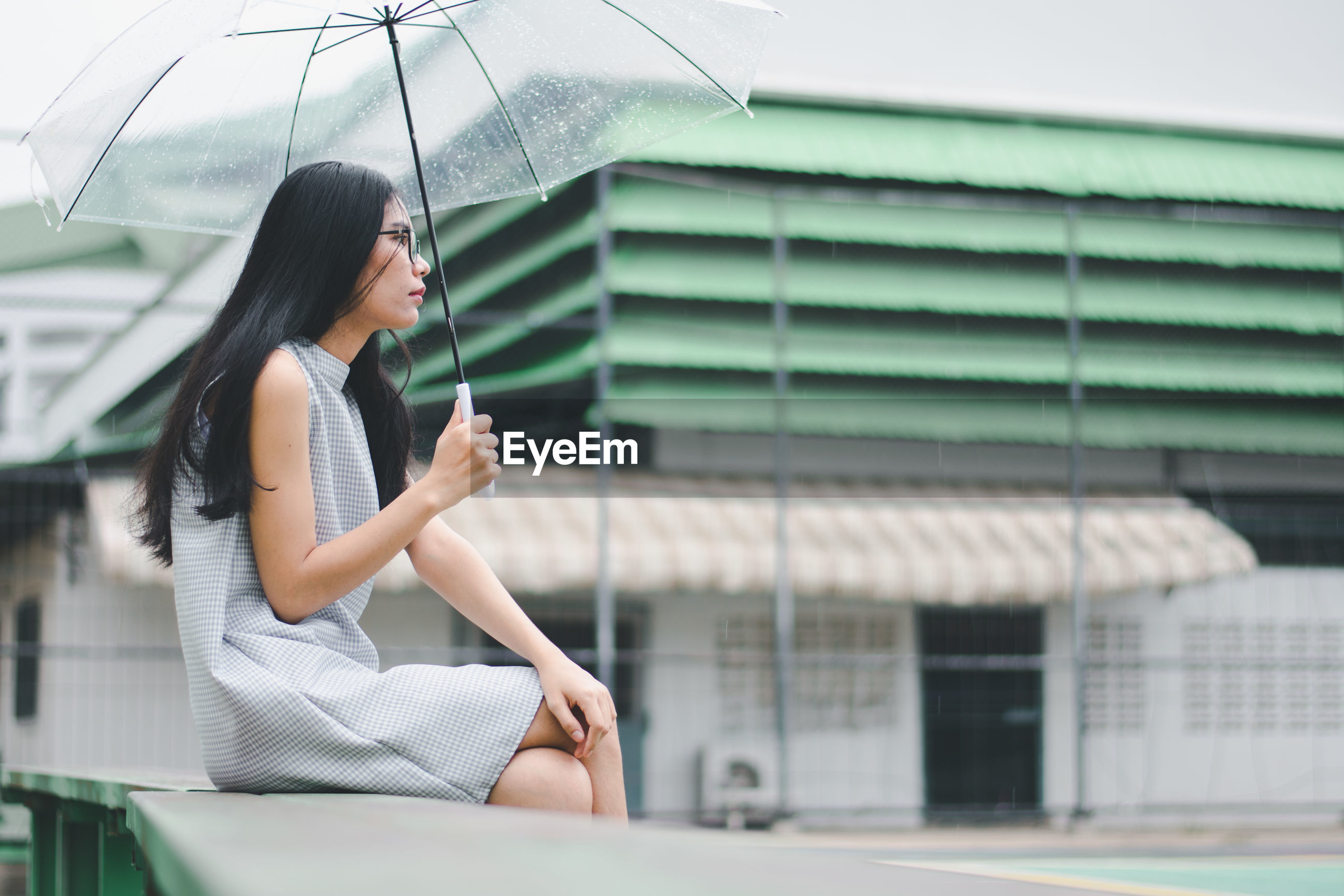 Side view of young woman holding umbrella sitting on retaining wall against building