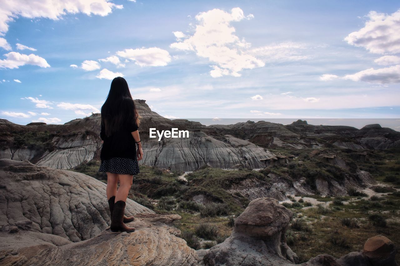 Rear view of woman standing on rock in badlands against sky