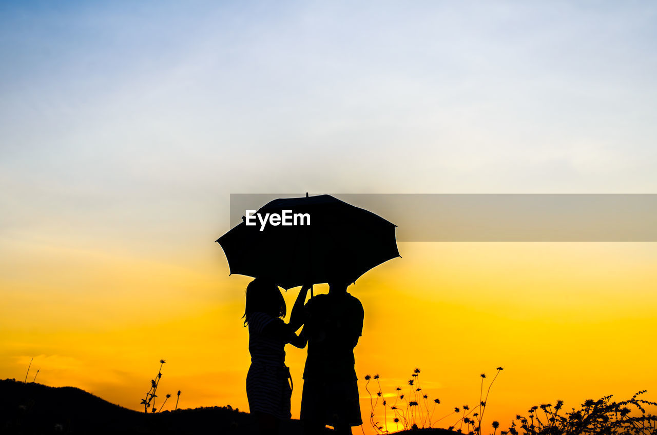 Silhouette Friends With Umbrella Against Sky During Sunset