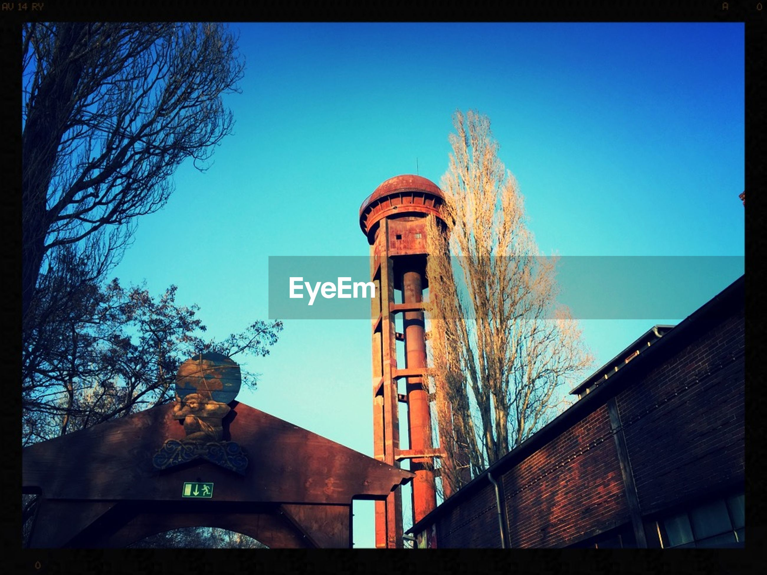 architecture, built structure, building exterior, low angle view, clear sky, transfer print, blue, tower, auto post production filter, tree, church, sky, place of worship, tall - high, religion, day, outdoors, copy space, no people