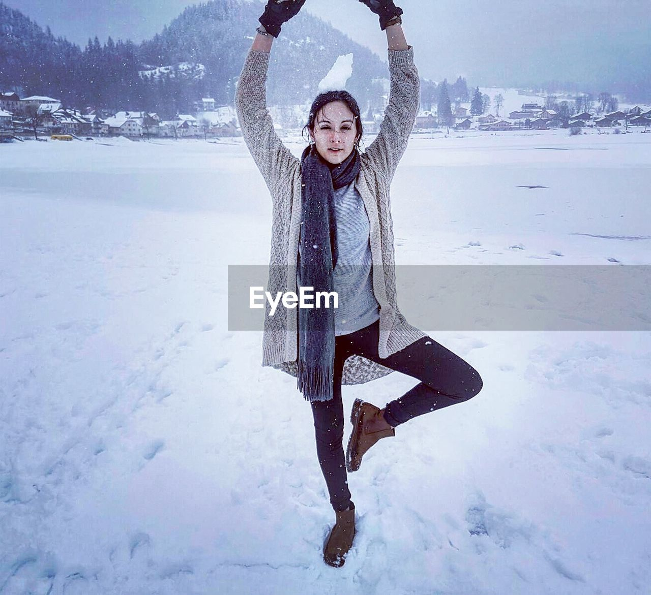 Smiling Woman Standing On One Leg With Arms Raised At Snow Covered Mountain