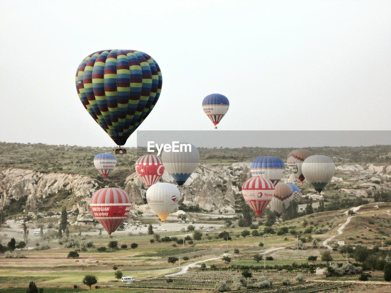 hot air balloon, adventure, outdoors, sky, mid-air, transportation, grass, landscape, day, ballooning festival, clear sky, nature, flying, air vehicle, no people, multi colored, beauty in nature, parachute