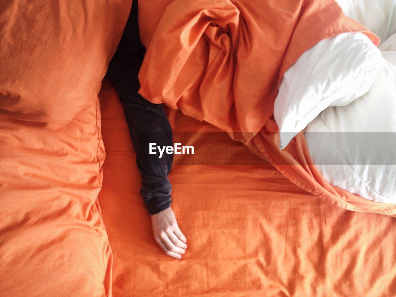 Man's Hand On Orange Bedding
