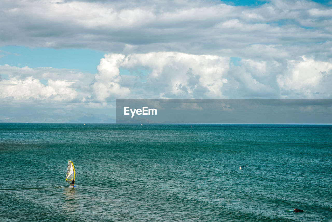 Scenic View Of Windsurfer And Surfer In Sea Against Sky