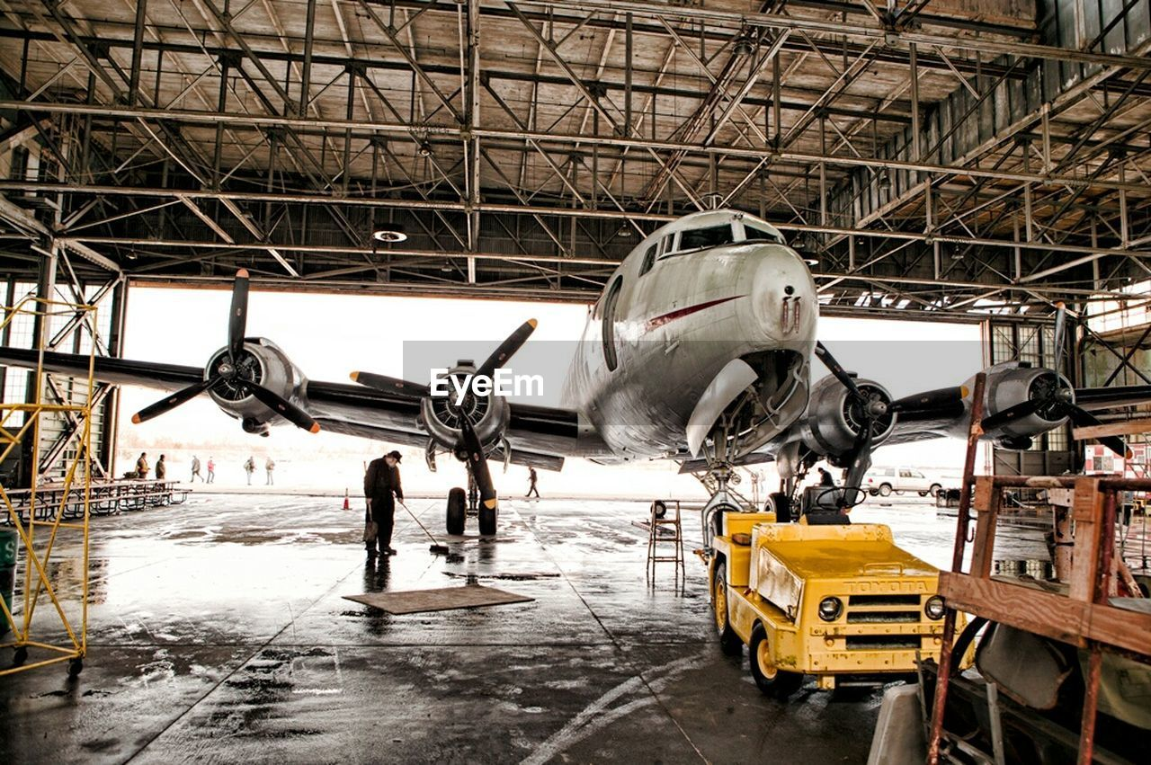 airplane, airplane hangar, transportation, aerospace industry, air vehicle, indoors, repairing, occupation, day, one person, airplane mechanic, people