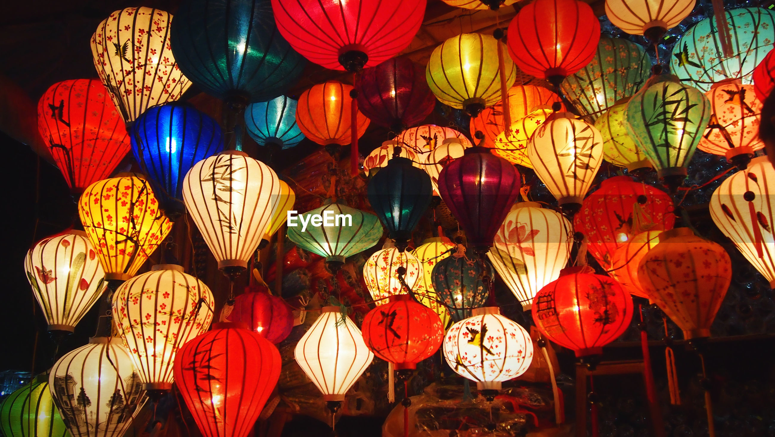 Illuminated lanterns hanging for sale in market at night