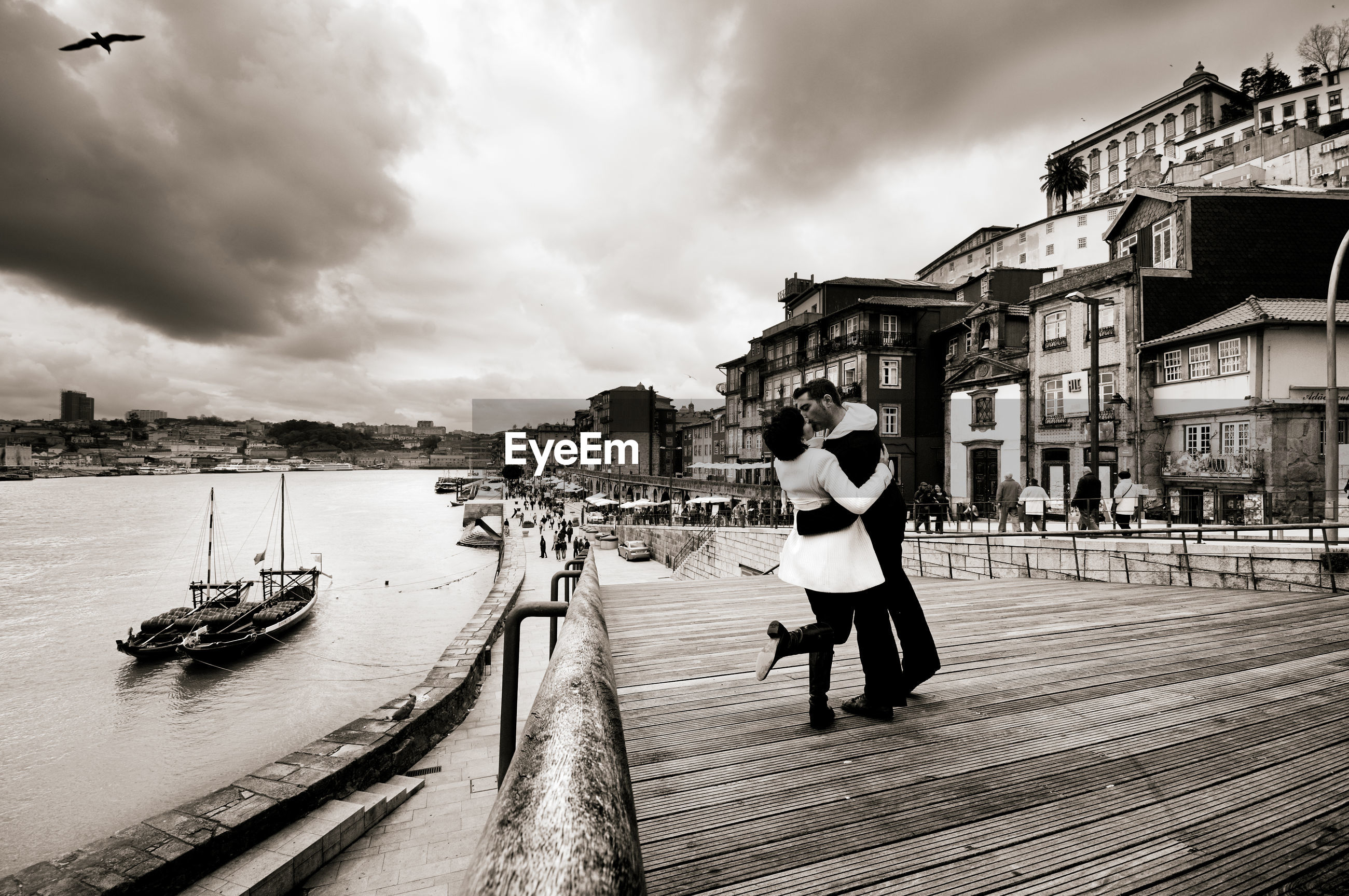 Couple kissing at beach in city against sky