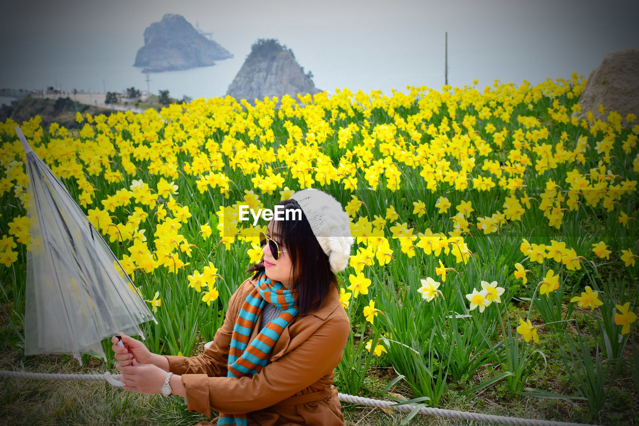 Woman holding umbrella against yellow flowering plants