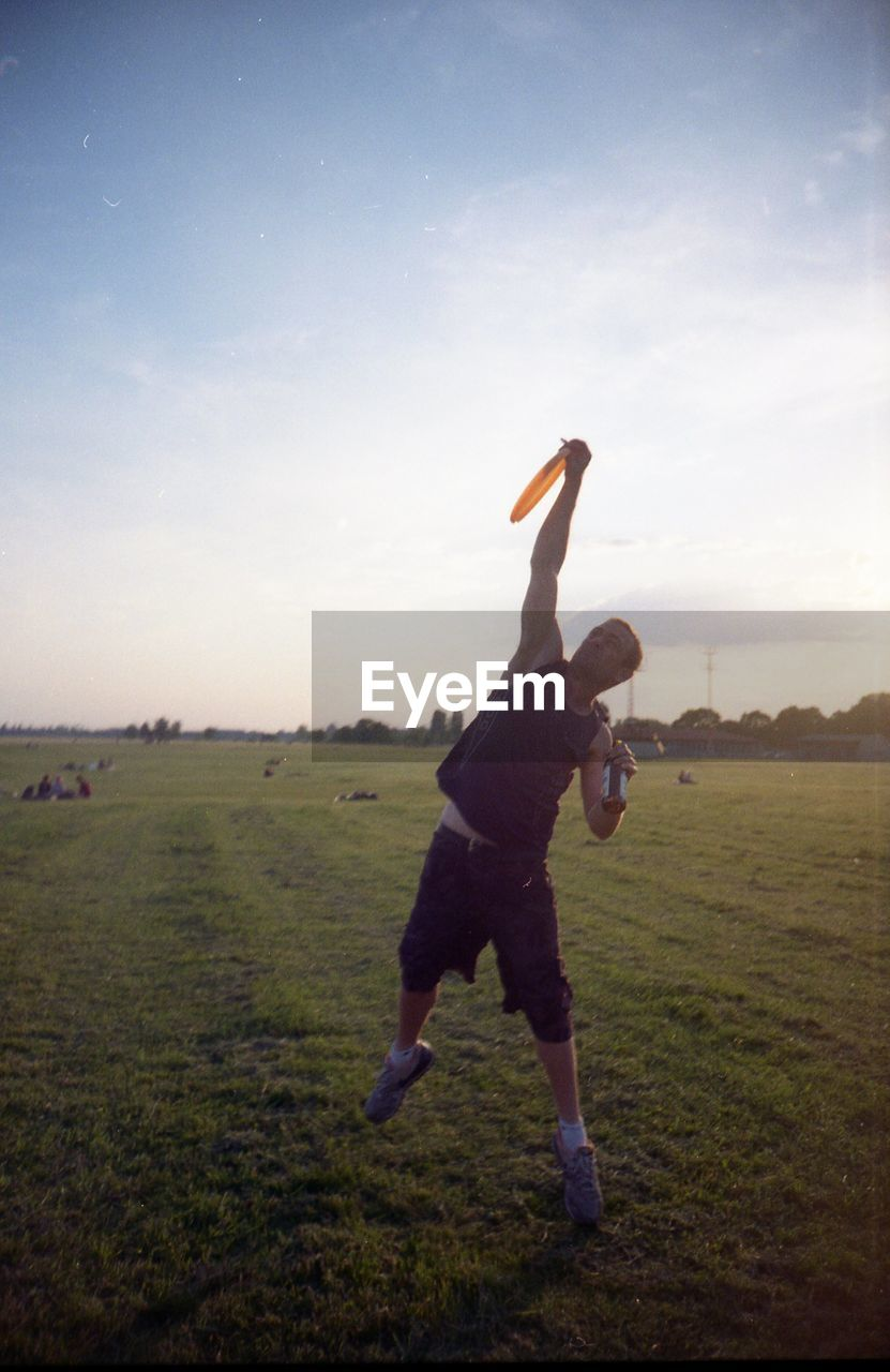 full length, field, grass, sky, one person, men, real people, landscape, day, sport, outdoors, lifestyles, nature, motion, golf, golf swing, golf course, one man only, energetic, young adult, golfer, adult, people